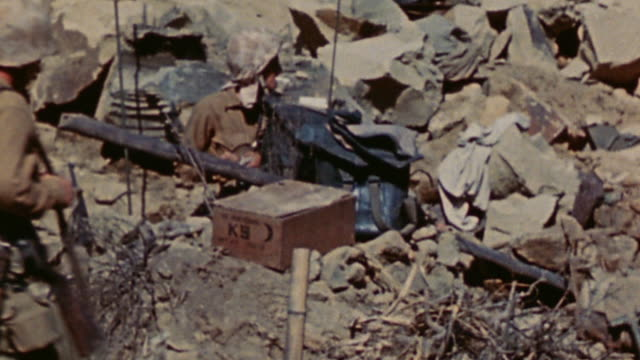radioman sitting behind his gear and marine infantry walking past rocky outcropping serving as cover / iwo jima japan - battle of iwo jima stock videos and b-roll footage