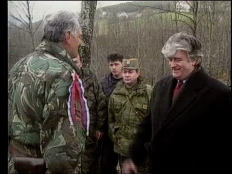 radovan karadzic shakes hands with general ratko mladic cms mladic looks thru binoculars then hands them to karadzic - ratko mladic stock videos & royalty-free footage