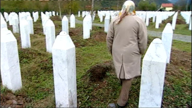 radovan karadzic will boycott his war crimes trial; itn reporter along thu cemetery with unidentified woman night various of muhamed durakovic... - ラドヴァン カラジッチ点の映像素材/bロール