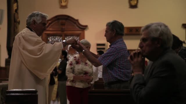 rafael ruiz delivers communion to parishioners during a service at the church of the little flower on february 11, 2013 in coral gables, florida.... - priest stock videos & royalty-free footage