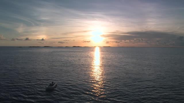 raft floating in sea at sunset - meerlandschaft stock-videos und b-roll-filmmaterial