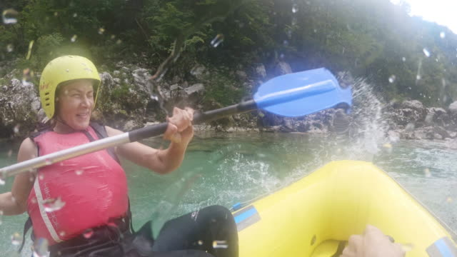 pov rafters having fun splashing water with paddles - inflatable raft stock videos & royalty-free footage