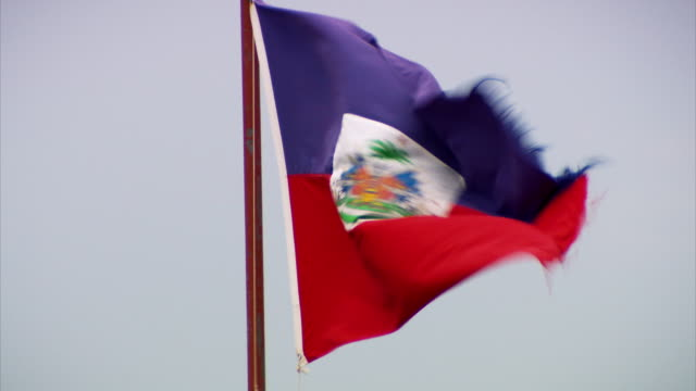 stockvideo's en b-roll-footage met a ragged haitian flag blows in the wind on a mast on the citadelle laferrière atop the bonnet a l'eveque mountain, nord department, haiti. - haïti