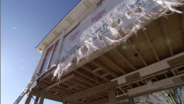 ragged tarps hang from the side of a house damaged by a hurricane. - 防水シート点の映像素材/bロール
