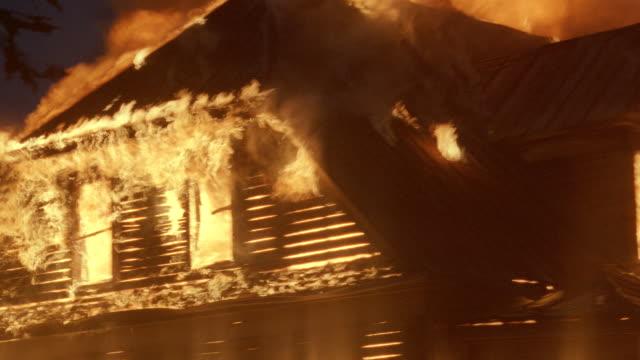 vidéos et rushes de a raging fire engulfs a farmhouse at night. - brûler
