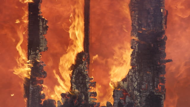 Raging fire seen through the charred remains of house structure supports