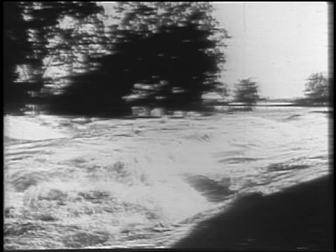 raging flood waters of mississippi river / house in background / newsreel - anno 1927 video stock e b–roll