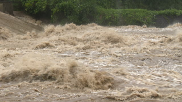 a raging river with rapids after typhoon noru dumps huge amount of rain on japan - wildwasser fluss stock-videos und b-roll-filmmaterial