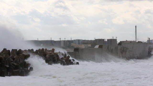 raging storm in harbor with oil tanks