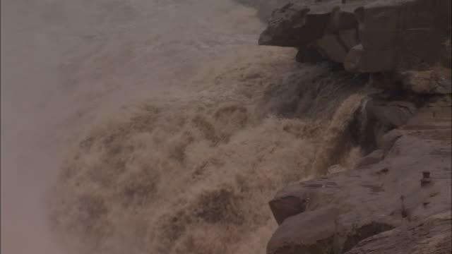 Raging torrent of water floods over falls, Hukou Falls.