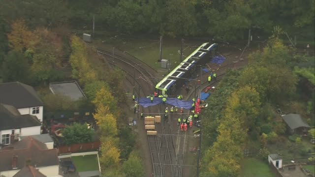at least 7 killed in croydon tram derailment; england: london: croydon: ext air views / aerials derailed overtruned tram with emergency services at... - 脱線点の映像素材/bロール