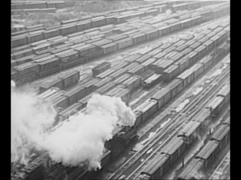 LS rail cars and steam engines at rail yard at Canadian port freight cars carry war materials for shipment overseas to Allied forces in World War II...