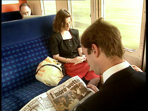 vídeos de stock e filmes b-roll de rail commuters compensation claims england southend barry unwin reading newspaper and waiting on platform for train as train comes in towards tms... - british rail