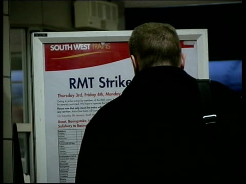 rail disputes; lib ext rmt official picket' armband int sign announcing industrial action bv man looking at board announcing rmt strike for southwest... - strike industrial action stock videos & royalty-free footage
