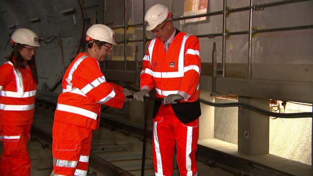 final piece of crossrail track laid england london whitechapel station int various of chris grayling mp and val shawcross using tool to install final... - クロスレール路線点の映像素材/bロール