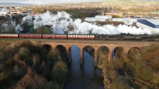 flying scotsman returns after 10 year refit; england: lancashire: ext air view / aerial flying scotsman train along tracks and crossing viaduct /... - steam stock videos & royalty-free footage