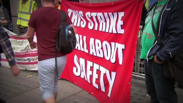 further strike action on southern rail / cost savings of phasing out train guards; england: london: victoria: ext slow motion banner held up by rmt... - strike industrial action stock videos & royalty-free footage