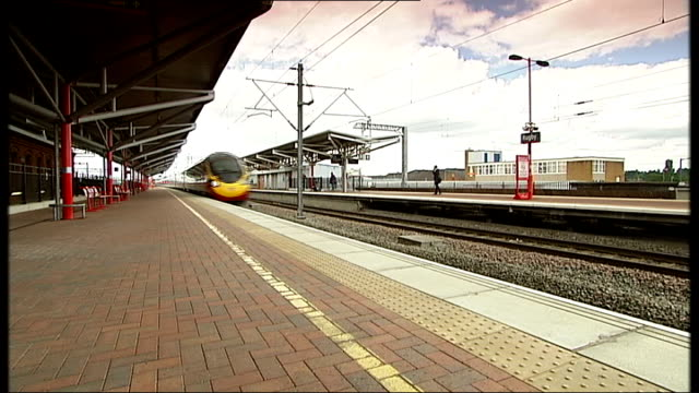 stockvideo's en b-roll-footage met government withdraws west coast franchise tender midlands rugby ext virgin high speed train speeding through station - west midlands