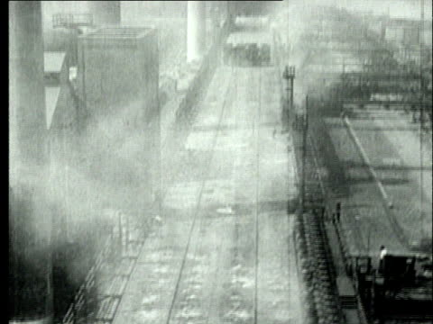 1927 B/W WS MONTAGE WS HA Rail lines running along coal mine plant and coke yard/ Row of 'Larry cars'  transporting coke along rail lines/ Pennsylvania