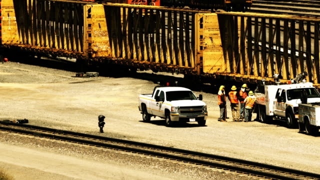 ws rail maintenance workers standing by tracks in rail yard as empty special cargo freight cars roll by / colton, california, usa  - tramway stock videos & royalty-free footage