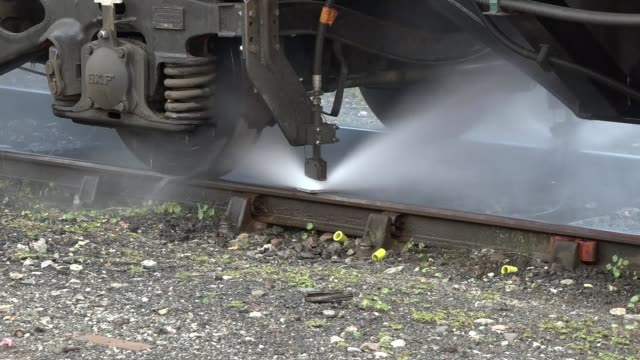 network rail employ new technologies to combat leaves on railway lines england ext close shot water jet spraying rail jet on specialist train... - washer stock videos and b-roll footage