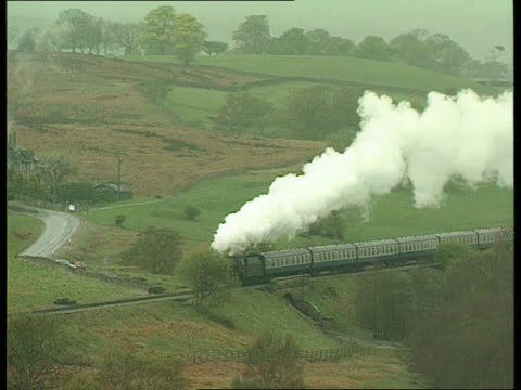 vídeos de stock e filmes b-roll de service levels announced itn england north yorks moors railway old style station as steam train arrives rl to colour and steam whistle is heard sot... - british rail
