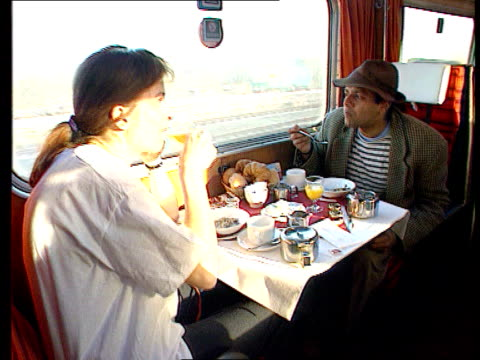 stockvideo's en b-roll-footage met rail sleeper service cuts delayed; int train tms side two women at table eating breakfast ext tlms west highlander towards and past lgv scenic... - seksueel overdraagbare aandoening
