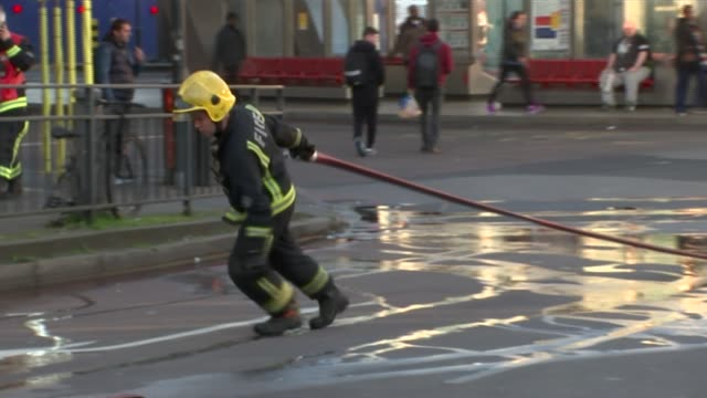 travel disruption caused by fire on tracks at vauxhall station firefighter dragging hose along rail worker at barrier outside station ambulance and... - itv london lunchtime news点の映像素材/bロール