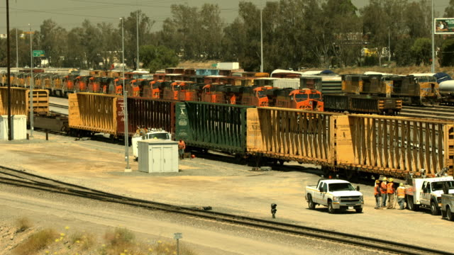 ws rail yard and interstate highway traffic in background / colton, california, usa  - railway track stock videos & royalty-free footage