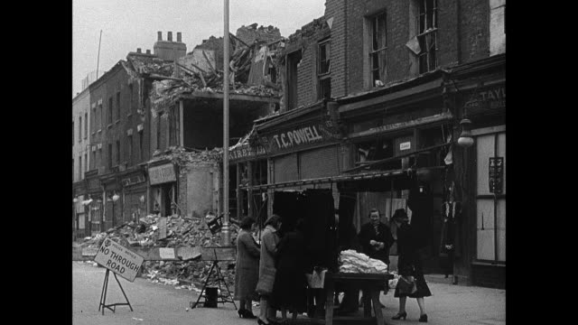 montage railing with tinsel decorations and hanging helmet, shops damaged by bombing but still cleaning up and carrying on, and stretcher bearers removing victim from rubble / england, united kingdom - tinsel stock videos & royalty-free footage