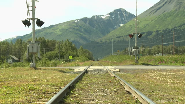"""railroad crossing shot straight on, pickup truck crosses left to right, forested and snow capped mountain in background, between seward and homer, kenai peninsula, alaska."" - homer alaska stock videos & royalty-free footage"