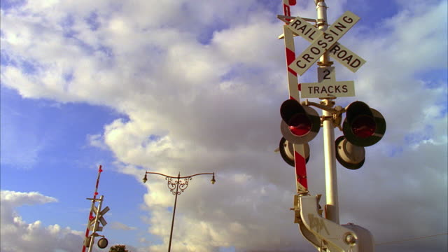 T/L CU LA Railroad crossing sign with freight train passing in background, white clouds rolling on sky, Santa Barbara, California, USA