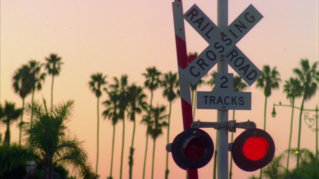 cu railroad crossing sign with palm trees in background at sunset, montecito, california, usa - level crossing stock videos & royalty-free footage