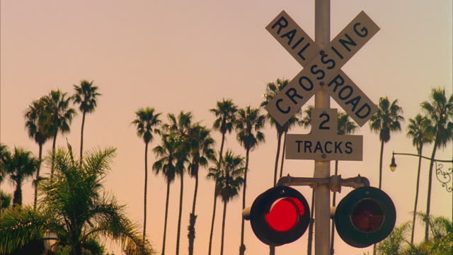 CU Railroad crossing sign with passenger train passing, Santa Barbara, California, USA