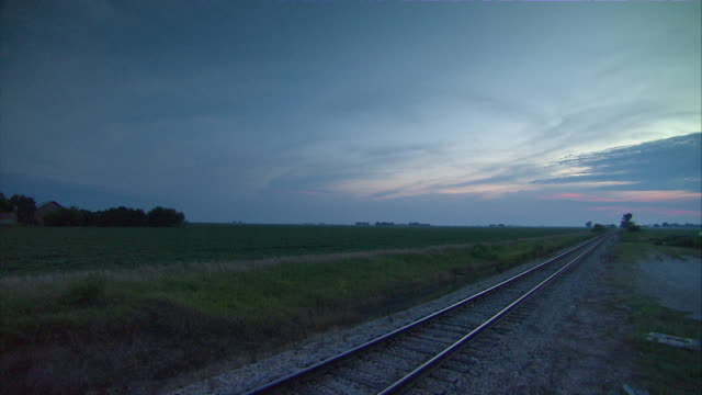 WS Railroad track and countryside fields under blue skies / Illinois, USA