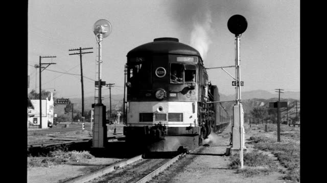 Railroad track in lightly populated suburban area of Los Angeles freight train pulled by Southern Pacific engine 4228 approaches and passes camera on...