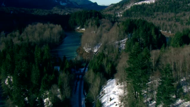 a railroad track winds along a lake in a forested valley. - evergreen stock videos & royalty-free footage