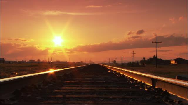 ws railroad tracks going straight off to vanishing point and setting sun / wyoming, usa - electricity pylon stock videos & royalty-free footage