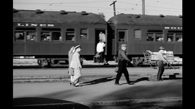 vídeos de stock e filmes b-roll de railroad tracks in southern california station / passengers including man in military uniform walk along platform train locomotive bearing southern... - estação de ferroviária