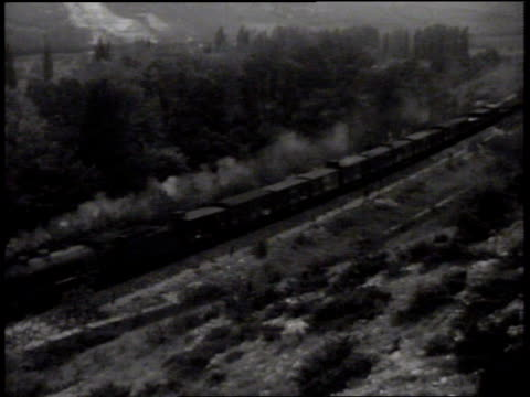 Railroad train moving on rural tracks Angled WS Freight train moving up frame DRAMATIZATION CU Male hands placing sticks of dynamite under railroad...