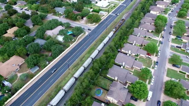 railroad train transportation aerial above homes and houses in suburb new modern development in central texas outside of austin, tx - modern rock stock videos & royalty-free footage