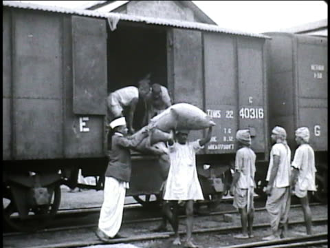 railroad warehouses line both sides of train track, angled male workers unloading sacks rice to males carrying away on heads, vs male inspector... - 荒い麻布点の映像素材/bロール