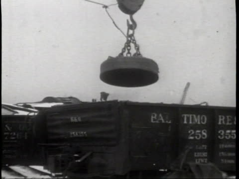 railroad worker directing a train at a scrap metal weighing station / a worker weighing the rail car / a large magnet pulling the scrap metal out of... - directing stock videos & royalty-free footage