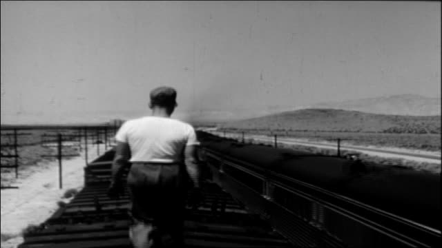 railroad worker walks atop train, 1950 - white shirt stock videos & royalty-free footage