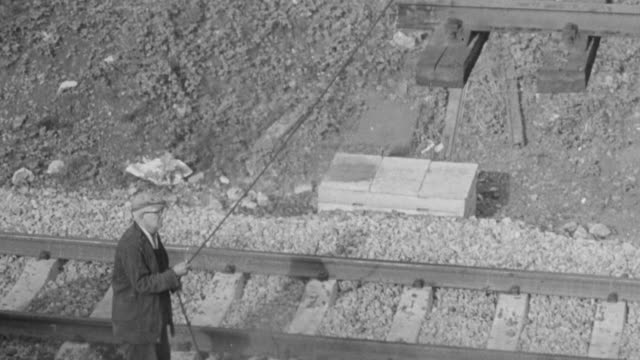 1965 montage railroad workers, using ropes, maneuvering tracks hoisted by a rail crane, and a train speeding along a completed track / united kingdom - bahngleis stock-videos und b-roll-filmmaterial