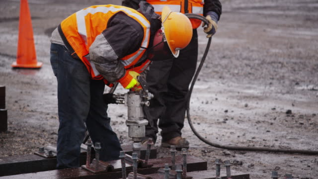 Railroad workers wearing safety gear, uses an industrial pneumatic drill to construct train tracks on a rainy day.