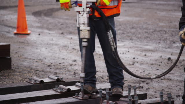 railroad workers wearing safety gear, uses an industrial pneumatic drill to drive large bolts to construct train tracks on a rainy day. - pneumatic drill stock videos & royalty-free footage