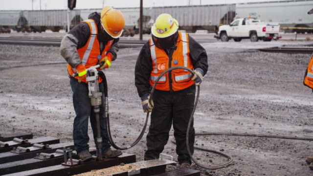 railroad workers wearing safety gear, uses an industrial pneumatic drill to construct train tracks on a rainy day. - pneumatic drill stock videos & royalty-free footage