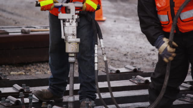 vidéos et rushes de railroad workers wearing safety gear, uses an industrial pneumatic drill to construct train tracks on a rainy day. - chemin de fer