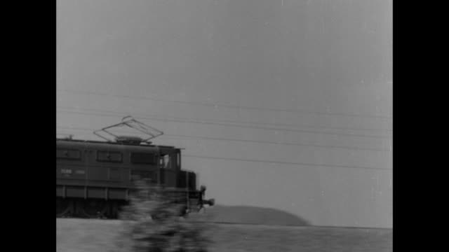 vidéos et rushes de montage railroads with locomotives hauling trains, rolling over tracks, cable connection on electrical train, passing rocky cliffs, and trains on bridges, mountain tracks, leaving tunnels, and cutting through valleys / switzerland - 1930
